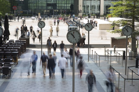 early morning workers rush past the clocks in londons docklands financial district