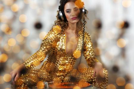 beautiful dancing woman in amazing gold costume djing