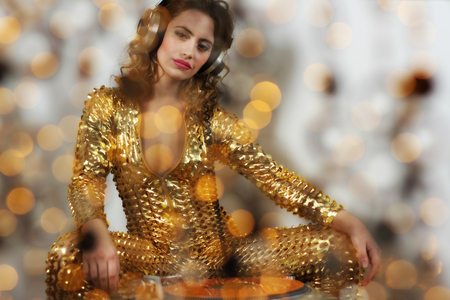 beautiful dancing woman in amazing gold costume djing photo