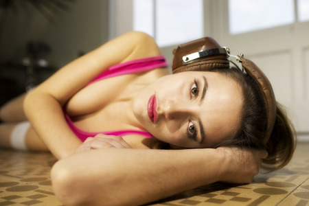 sexy headphones: beautiful woman in pink body listening to music on the floor