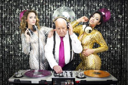 놀라운 할아버지의 DJ와 그의 두 beauitful 고고 댄서 스톡 콘텐츠