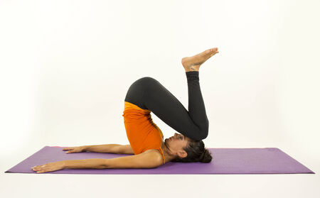 unwind: young woman practices yoga moves and positions in a studio setting Stock Photo
