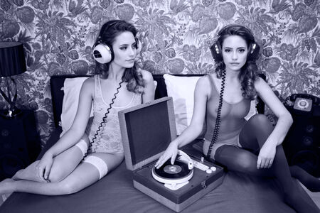 fantastic conceptual image of a beautiful sexy disco woman on a bed playing records filmed twice interacting with herself.  photo
