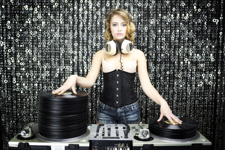 beautiful female dj with pile of vinyl records