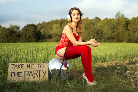 beautiful sexy party woman in lingerie sitting on a discoball in a field with a sign saying take me to the party 版權商用圖片