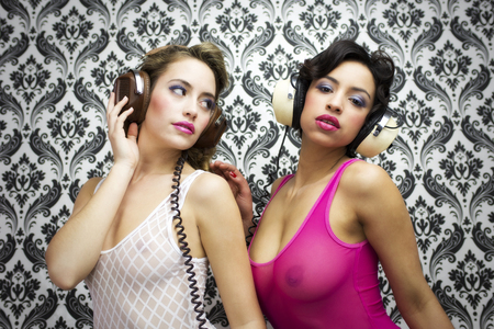 two beautiful sexy disco women in a bar lounge setting with headphones photo