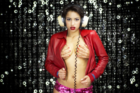 Beautiful breasts: sexy beautiful latino woman dancing with headphones and an open red leather jacket showing part of her body. there is an extra pair of hands covering her breasts
