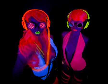 future twin: two sexy female disco dancers posing in UV costume