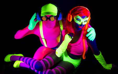 two cool disco glow characters pose in UV costume Stock fotó
