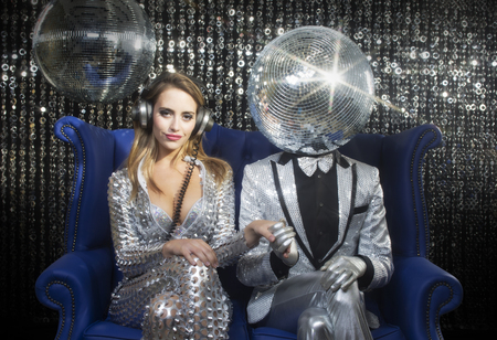 introducing mr and mrs discoball. two cool club characters dance and pose in a nightclub setting Standard-Bild