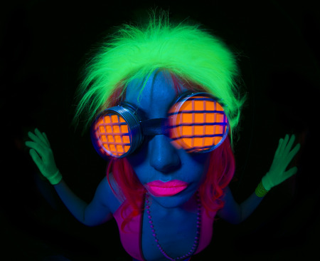 space age: close up shot of sexy female disco dancer poses in UV costume Stock Photo