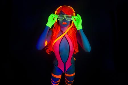 Atractivo bailarín del disco femenino posa en traje UV Foto de archivo - 49381713