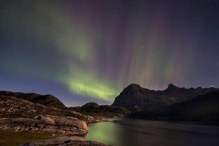 geomagnetic: stunning aurora borealis captured in norway in mountain landscape