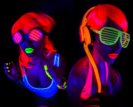 neon light: two sexy female disco dancers posing in UV costume