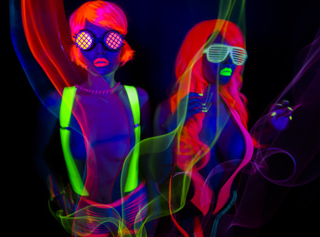 two sexy female disco dancers posing in UV costume