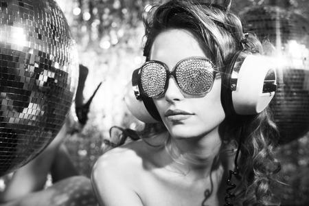 prachtige sexy disco vrouw met kristallen bedekte zonnebril poses op een bed, omringd door discoballen Stockfoto