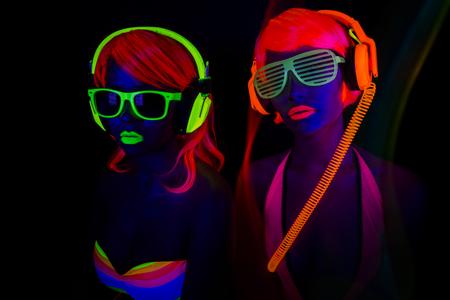 fiestas electronicas: dos bailarines del disco femenino atractivo que presenta en traje UV