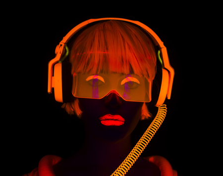 close up shot of sexy female disco dancer posing in UV costume with headphones Standard-Bild