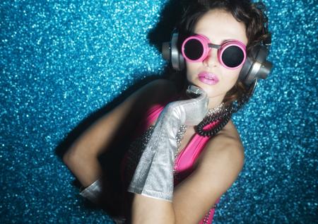 gogo girl: sexy Disco-Tänzer in rosa Bikini vor blauem Hintergrund