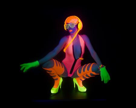 sexy female disco dancer poses in UV costume