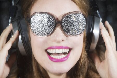 sexy woman disco: beautiful sexy disco woman, listening to music with sparkle covered sunglasses. Perfect for stylish club, disco and fashion events