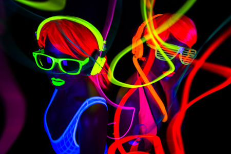 Fiesta: dos bailarines del disco femenino atractivo que presenta en traje UV