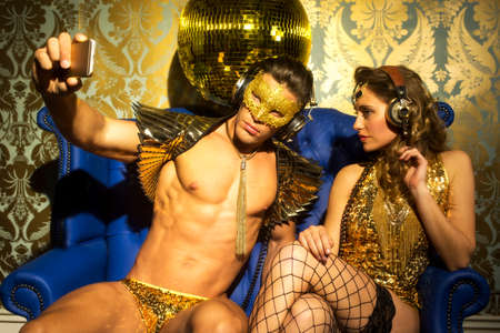 erotic fantasy: Two gold sexy disco caracters taking a selfie with a mobile phone Stock Photo