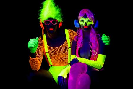 セクシーなカップル ディスコ パーティー ダンサー UV 衣装でポーズをとって
