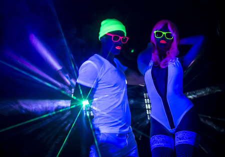 couple disco party dancers posing in UV costume