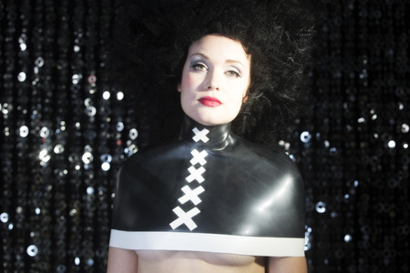 fancy dress party: freaky sexy disco woman with big wig and latex top. Perfect for stylish club, disco and fashion events Stock Photo