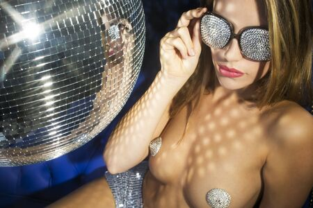 erotic fantasy: stunning sexy disco woman on a blue leather chair surrounded by disco balls diamond sunglasses Stock Photo