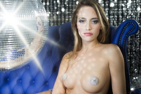 mujeres eroticas: impresionante mujer atractiva del disco en una silla de cuero azul rodeada de bolas de discoteca