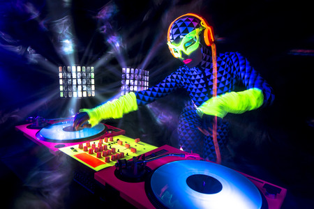 alien women: sexy female DJ mixes in a club  in UV fluorescent costume Stock Photo