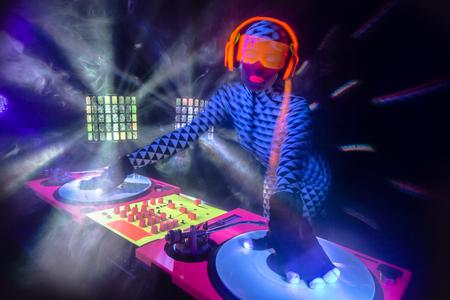 alien robot: sexy female DJ mixes in a club  in UV fluorescent costume Stock Photo