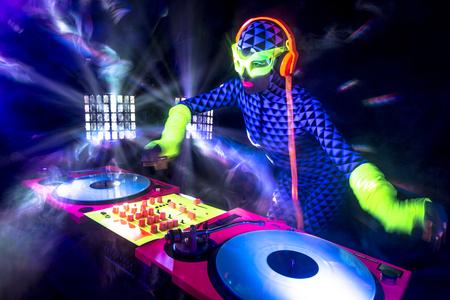 fluorescent light: sexy female DJ mixes in a club  in UV fluorescent costume Stock Photo