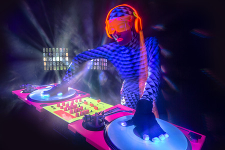 sexy female DJ mixes in a club  in UV fluorescent costume Stock fotó
