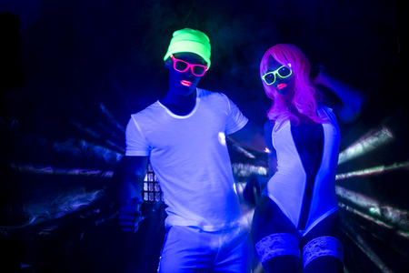 sexy couple disco party dancers posing in UV costume
