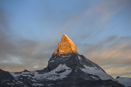 dawn, sunrise scene of the amazing matterhorn mountain in the Swiss Alps. the sky lights up in an incredible display of colour and the shadow lowers over the mountain