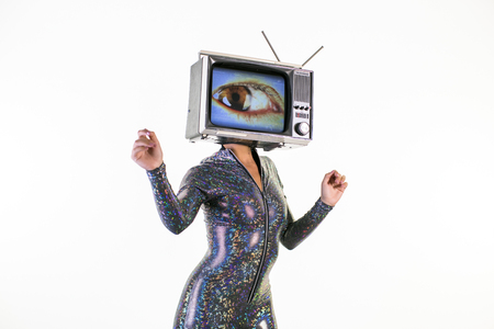 amazing woman dancing and posing with a television as a head. the tv has a large eye on it