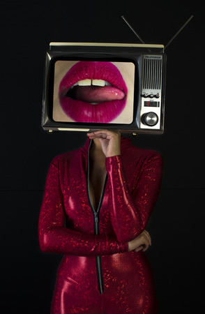 amazing woman dancing and posing with a television as a head. the tv has an image of luscious women's lips on it