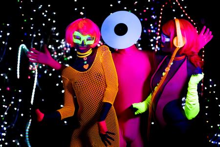 3 cyber glow raver friends filmed in fluorescent clothing under UV black light