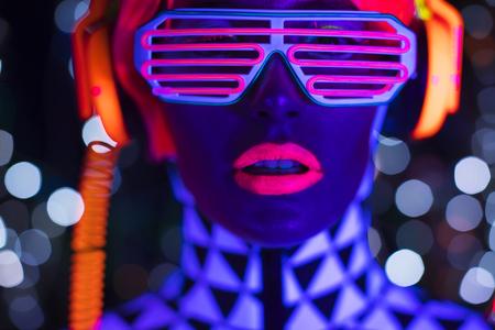 섹시한 사이버 방탕 한 여자의 환상적인 비디오 UV 검정 빛 아래 형광 의류에서 촬영