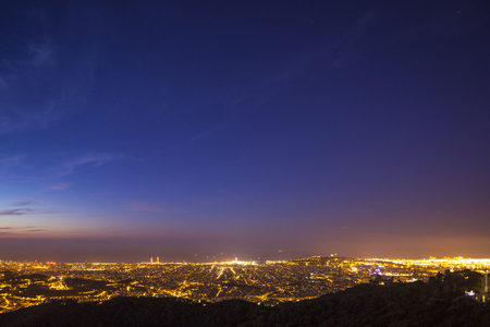 barcelona skyline all lit up, just before sunsirse from tibidabo mountain