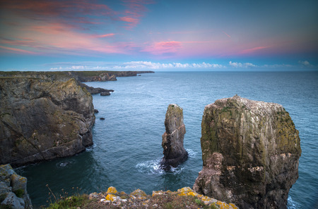 stunning sunset of the green bridge, a natural rock arch on the coast of pembrokeshire, wales, UK