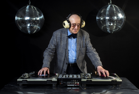 an amazing grandpa DJ, older man djing and partying in a disco setting