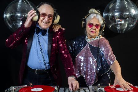 eine tolle Oma und Opa, ein älteres Paar, das in einer Disco-Umgebung auflegt und feiert party