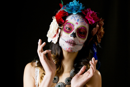 beautiful woman with custom designed candy skull mexican day of the dead face make up Stock Photo