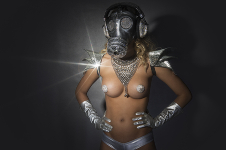 woman dances in silver body paint with a gas mask covered in sparkling crystals. this is a special handmade item from our studio. how to survive the apocalypse in bling bling style Stock Photo