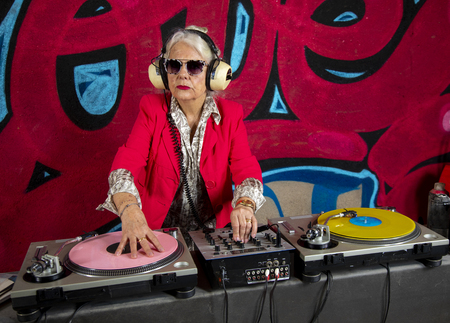 awesome grandma dj in front of graffiti wall