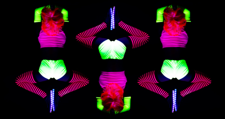 amazing female yoga instructor doing a head stand wearing fluorescent clothing under UV black light